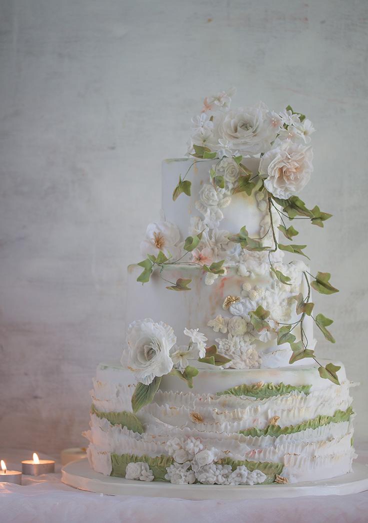 Tort weselny biały z białymi kwiatami i drobnymi listkami