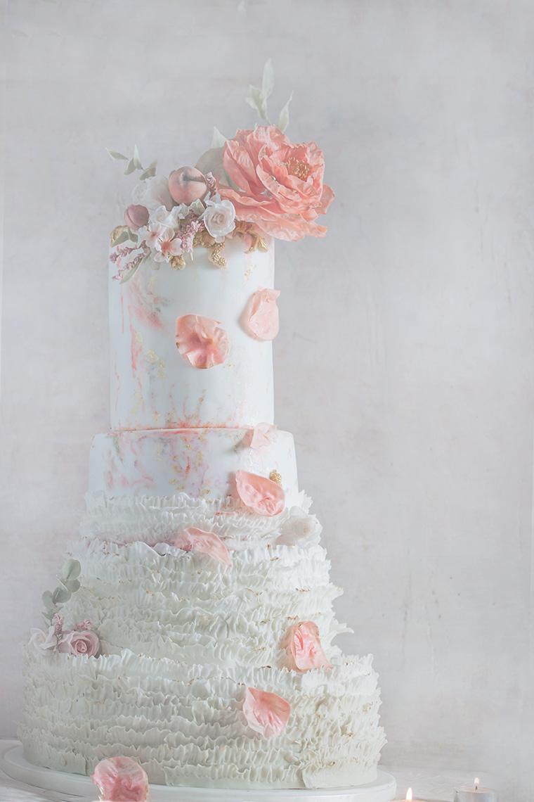 Biały tort ślubny z płatkami kwiatów