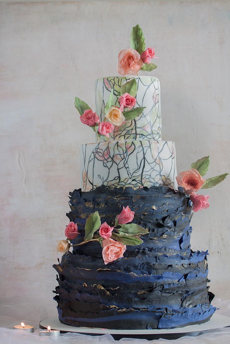 Biało-granatowy tort weselny z różowymi kwiatami