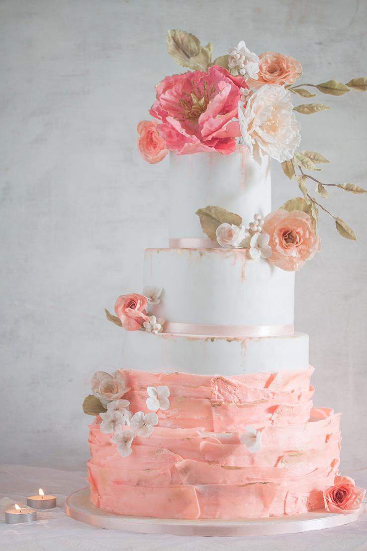 Biało-różowy tort z dużym przystrojeniem kwiatowym