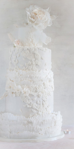 Śnieżnobiały tort weselny z kwiatem